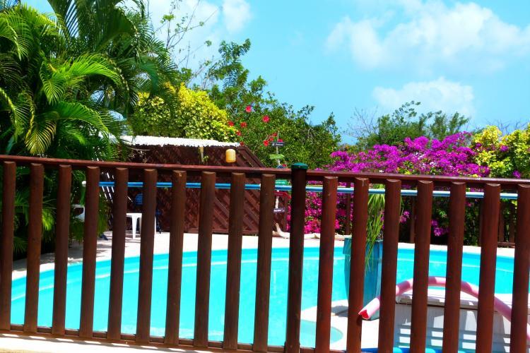 La piscine est sécurisée par une enceinte en bois et une barrière équipée d'une sécurité enfant.